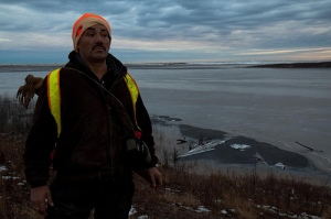 A hunter in Northern Alberta stands in front of a Tar Sands oil spill. Photo by Ben Powless.